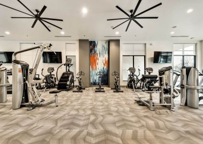 Luxury commercial-sized fitness studio with ceiling fans, and flat screen televisions.