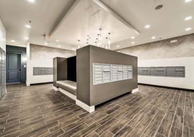 Delivery lockers and mail room with hardwood tile flooring and custom light fixtures.