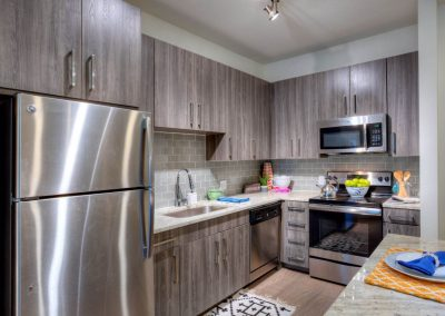 Luxury Kitchen Featuring Upscale Cabinets, Stainless Hardware, Granite Countertops, and Subway Tile Backsplash