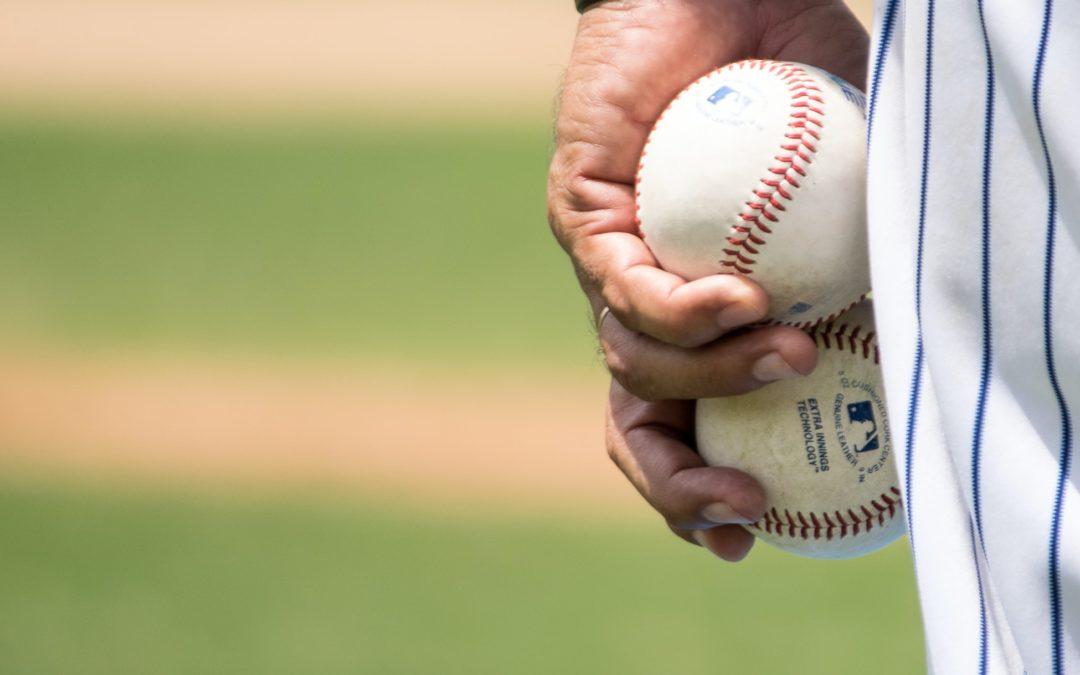 Man Holding Two Baseballs